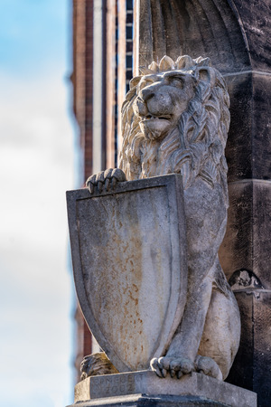 Carved stone lion with heraldic shield on the exterior facade of a historic brick building with a view to a cloudy blue sky. Banco de Imagens