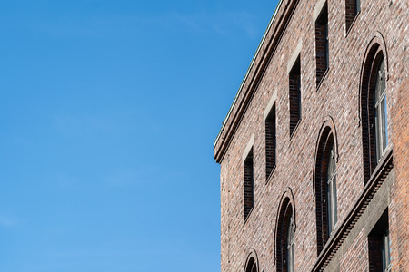 Top corner of brick building facade with arched windows, viewed from low angle against clear blue sky.