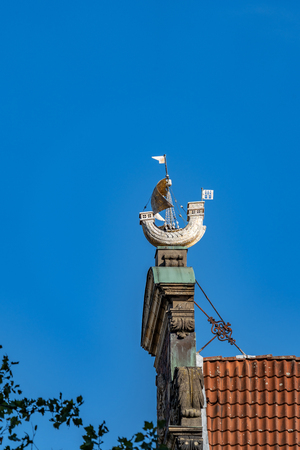 Gable mounted historic sailboat on building exterior in Hamburg, M?nckebergstra? ee, Germany against a sunny blue sky.