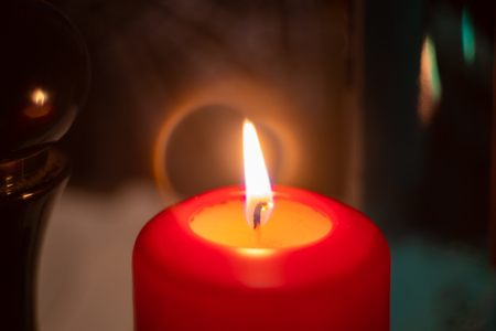 Close-up on red decorative candle with burning flame. Faded fire reflected in dark background Banco de Imagens