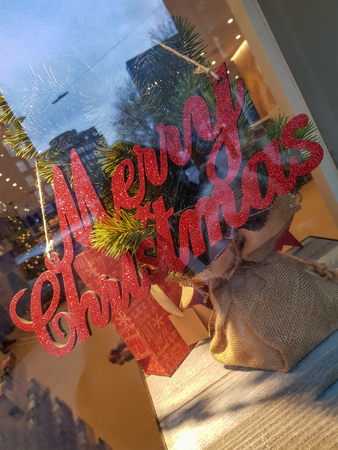 Red Merry Christmas sign decoration in window shop, placed over sackcloth bag on the shelf, with decorated gifts and fir branches. City office buildings in the street is reflected in shop window.
