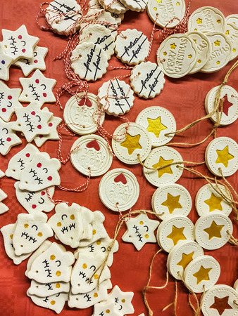 Assortment of Christmas decorations on red with bells and discs decorated with hearts, stars and seasonal greetings in a full frame overhead view