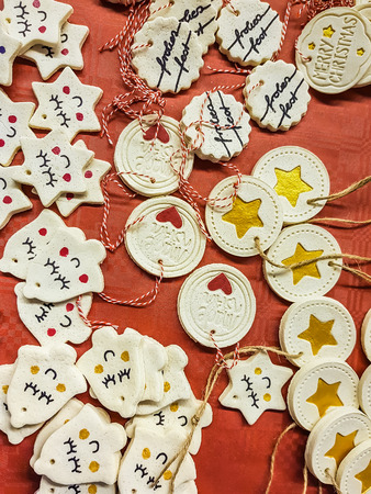 Collection of Christmas decorations with hangers scattered on a red background with bells and discs with hearts, stars and seasonal greetings