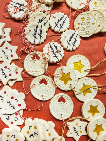 Assorted shaped hanging Christmas decorations scattered over a red background with bells and medallions with hearts, stars, and seasonal greetings