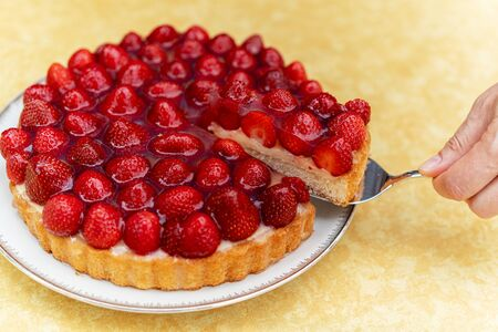 Strawberry cake, photographed in the garden, from which a piece is taken, arranged on a yellow tablecloth.