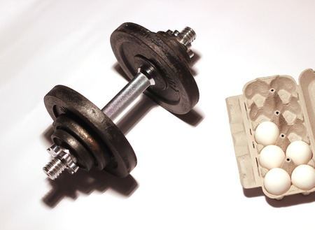 muscle formation:   Dumbbell and a half filled package of eggs as a symbol for fitnessbodybuilding.