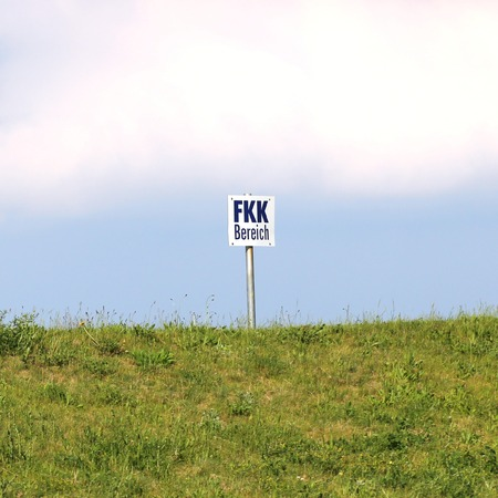 nudist:   Hill with a sign indicating an FKK  Nude bathing  area