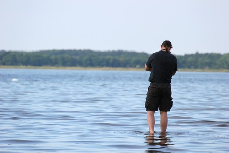 cross armed:   Person standing in shallow water staring at the sea