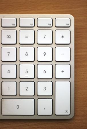 numpad:   Numpad of an Apple keyboard on wooden desk
