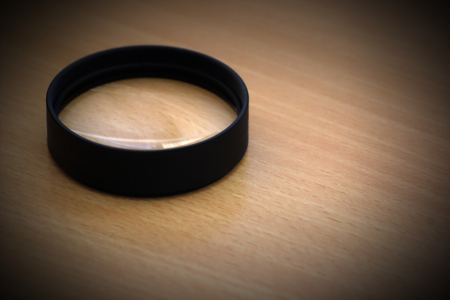 vignetting:   Close up lens on wooden desk. Vignetting was added. Stock Photo