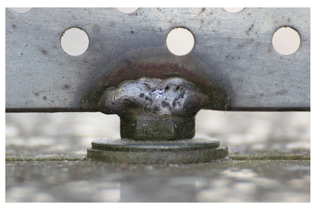 Close up of a weld seam holding metal panel with holes. photo