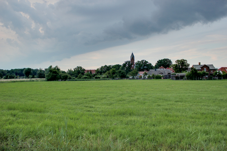 greifswald:   Rural landscape and town during weather change with heavy clouds and blue sky.