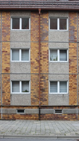 image created 21st century:   Typical windows in a plattenbau style building from eastern Germany. The Street can be seen at the ground. Stock Photo