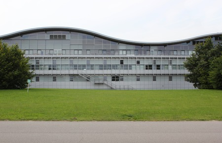 assembly point:   Modern scienceindustry building with wave shape. An assembly point sign can be seen on the left.