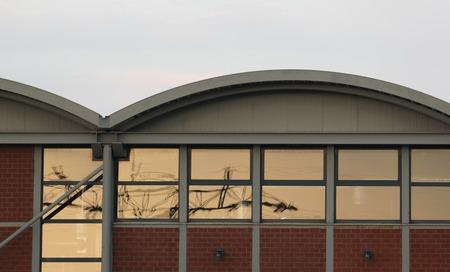 bedrijfshal:   Windows with orange reflection of power line on an industrial building. Stockfoto