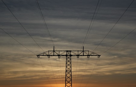 image created 21st century:   Symmetrical view on a high voltage power line in the evening. The sky shows splendid colors.