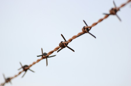 Barbed wire in evening sun, reaching from corner to corner. photo