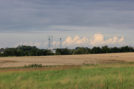 contrasty:   Agricultural landscape with industry building and contrasty clouds.