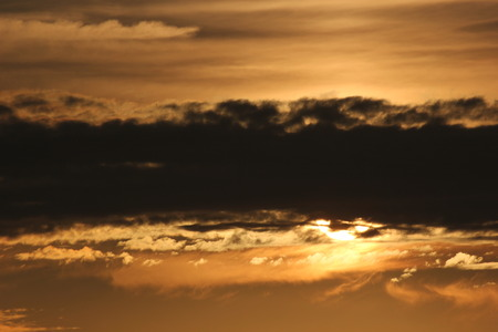 Sun behind band of clouds with big contrasts in light intensity. photo