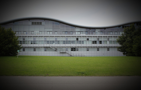 assembly point:   Modern scienceindustry building with wave shape. An assembly point sign can be seen on the left. Vignetting was applied.