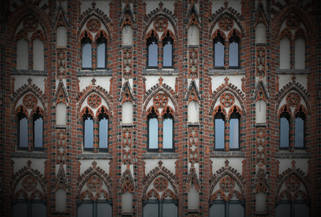 image created 21st century:   Facade of a historic city center building in the style of brick gothic with many windows. This architectural style was used from the 12th to the 16th century. Vignetting was applied.