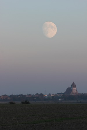 waxing gibbous: Meadows with misty view on the city of Greifswald, Mecklenburg-Vorpommern, Germany.