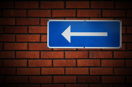 red handed: Arrow sign on a red brick wall.