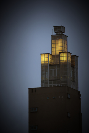 image created 21st century: Look-out tower in the evening with light in the glass section at the top.