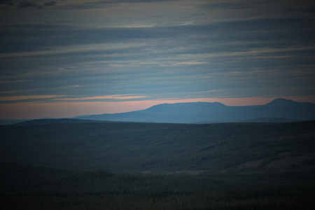 Different shades of blue and orange over forest landscape seen from a Swedish mountain. Stock Photo