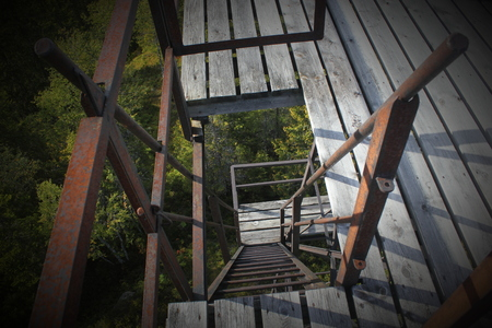 acrophobia: Looking down on steep and rusty ladder steps.