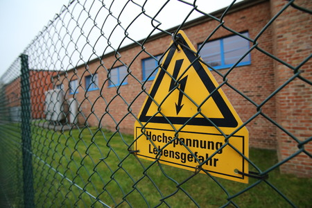 electroshock: High voltage sign on a fence in Germany. The lower lines mean high voltage life danger.