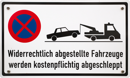 towed: German stopping restriction sign, translation: Illegally placed vehicles will be towed liable to pay costs. Stock Photo