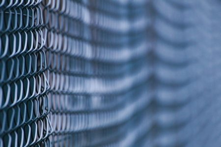 image created 21st century: Abstract shot of a green wire mesh fence with defocusing effect.