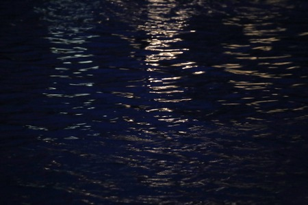 image date: Reflections of yellow light on water in the night. Stock Photo