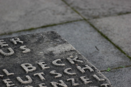 generic location: Detail of memorial for resistance fighters against National Socialism in WWII. Unidentifiable fragments of names can be seen on the stone panel.