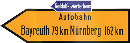 autobahn: Old design (1937) of a German direction sign showing the way to the Autobahn and Bayreuth and Nuremberg. The text on the blue sign says: Refueling service - attendants house. Stock Photo