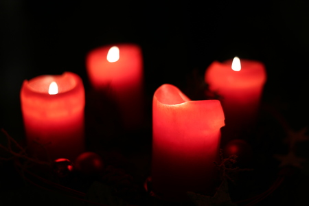 image created 21st century: Four red christmas candles with selective focus effect.