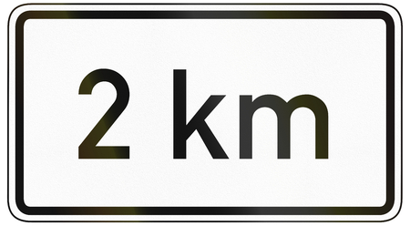 specify: German traffic sign additional panel to specify the meaning of other signs: 2 kilometers ahead. Stock Photo