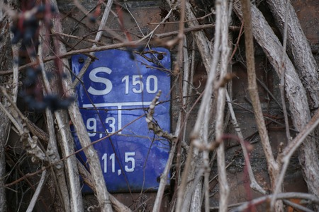 image created 21st century: Historical gate valve sign for water supply in Germany, nearly overgrown by vines. The information on the sign give the type and position of a nearby underground gate valve. Stock Photo