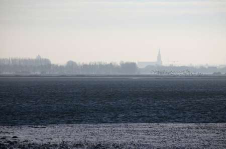 greifswald: Misty view on Greifswald from the north with dark blue water.