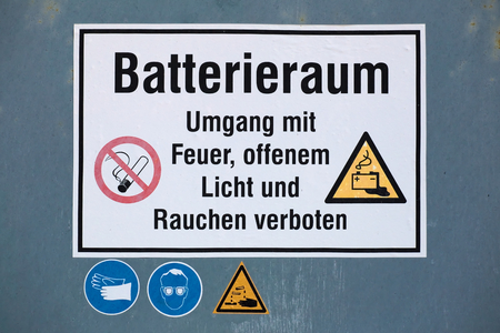 Warning sign on battery room with various symbols. The text means: Battery room - Fire, open flame, and smoking are forbidden. photo