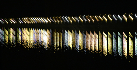 staggered: Row of lights reflected on a river. The lights are staggered creating a dense arrangement.