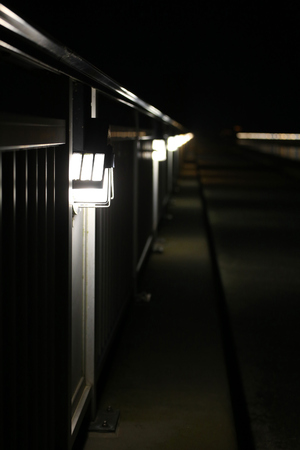 image created 21st century: Long row of lamps a railing besides the street.