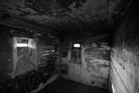 confined space: View in a small confined room in an old WWII bunker near Lostau, Saxony-Anhalt, Germany. Black and white image.
