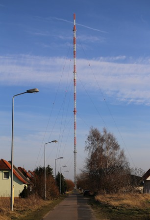 image created 21st century: Small street leading to a red and white radio tower
