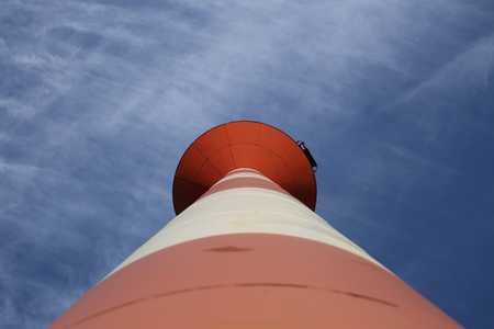 image created 21st century: Modern red and white striped lighthouse on blue sky seen from an unusual wide angle directly from below. Rostock, Mecklenburg-Vorpommern, Germany
