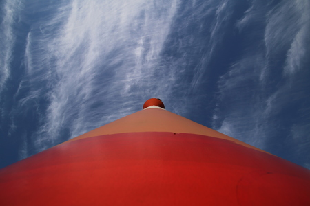Modern red and white striped lighthouse on blue sky seen from an unusual wide angle directly from below. Rostock, Mecklenburg-Vorpommern, Germany