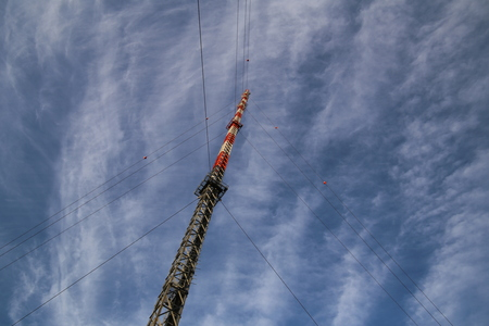 medium shot: Red and white radio tower in unusual angle