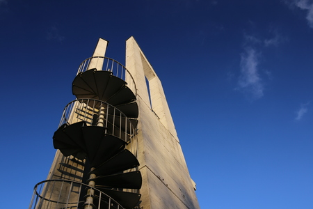 image created 21st century: Lookout tower with spiral staircase seen from below. The sky is darkened due to the use of a polarization filter.