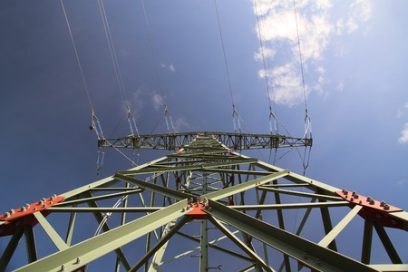 distorted image: Wide angle view of a high voltage line pylon and dark blue sky from below. Stock Photo